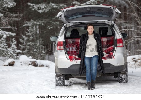 Adult woman in mink fur coat sitting in trunk of her car under opened back door, wintry forest #1160783671