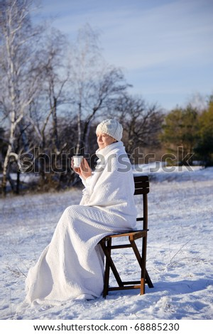 adult woman in white, with mug in his hands  on a snowy forest background, bright sunny frosty day.