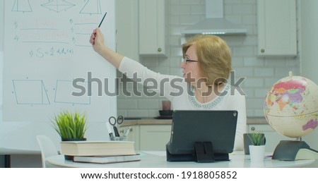 Adult woman involved in distant math lesson, enjoying studying remotely communicating with teacher by tabletPC video call. Online distance learning education lesson concept.