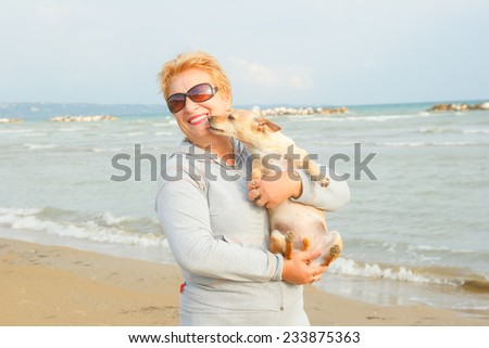 Adult woman is holding her dog. Retired woman standing on the shore of the sea or ocean. Old woman spends time with his dog on the background of the sea. Walking the dog on the beach. Tourism. Dog.