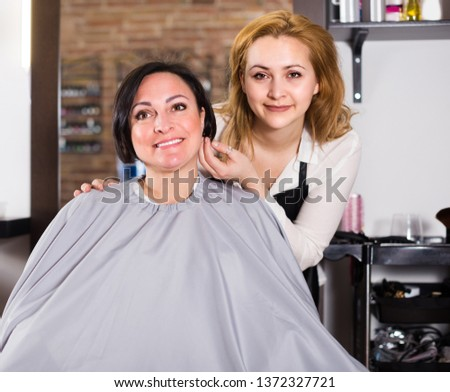 Adult woman likes very much her hairdress in hairdressing salon.