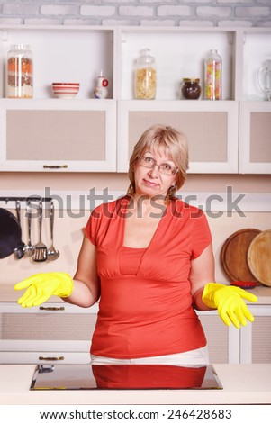 Adult woman makes cleaning the kitchen. Woman in yellow gloves cleaning the kitchen. Cleanliness, order, shine, clean, shiny, cleaning after the holidays at home kitchen. attractive middle aged woman.