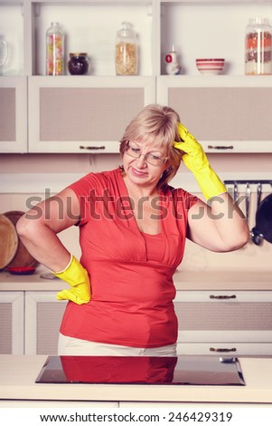 Adult woman makes cleaning the kitchen. Woman in yellow gloves cleaning the kitchen. Cleanliness, order, shine, clean, shiny after the holidays at home kitchen. Attractive middle aged woman. vintage