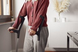Adult woman on crutches at home. Fracture of the leg or foot. Concept of rehabilitation and healing. Orthopedics and Traumatology. Unrecognized person