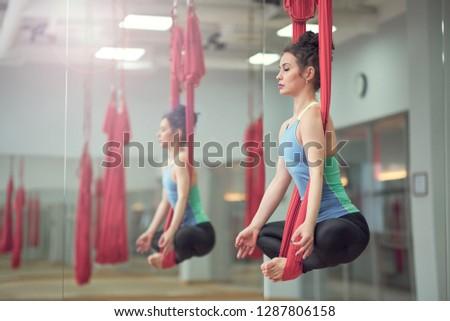 Adult woman practices aero anti-gravity yoga position in studio. Inversion bow pose in aero anti gravity yoga. Aerial exercises