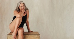 Adult woman smiling while posing in her natural body. Confident woman in black underwear embracing her aging body. Mature woman sitting alone against a studio background.