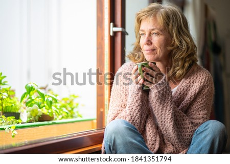 Adult woman taking tea pensive looking out the window ストックフォト ©