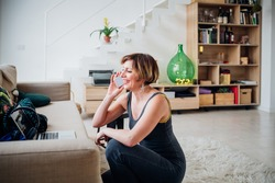 Adult woman using smartphone calling friends having fun - Cheerful woman at home laughing relaxing having fun