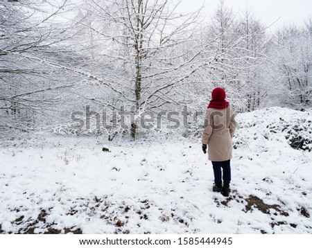Adult woman walking in winter forest. Snowy nature landscape. Activity relax on fresh air concept.
