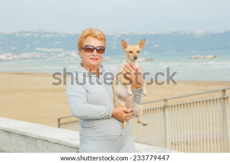 Adult woman walking with a dog on a sea beach. Walking with a pet. Dog - a friend of pensioners. Beach, sea, animals, walk, ocean, fresh air, resort - the concept of lifestyle old woman retired.