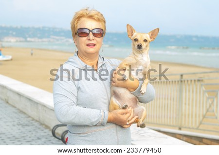 Adult woman walking with a dog on a sea beach. Walking with a pet. Dog - a friend of pensioners. Beach, sea, animals, walk, ocean, fresh air, the resort - the concept of lifestyle old woman retired.