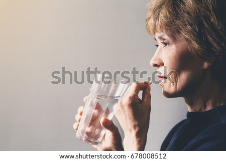Adult woman with a pill and a glass of water / healthcare concept #678008512