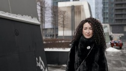 adult woman with extravagant hairstyle is walking in city at winter, portrait of townswoman dressed fur coat