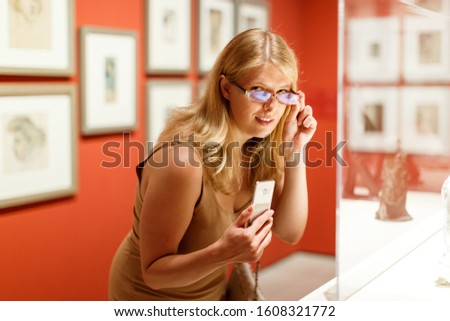 Adult woman with glasses and mobile phone looking at exhibits in glazed stands in art museum