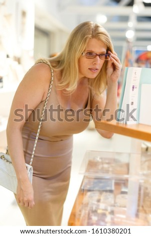 Adult woman with glasses looking at stands with exhibits in historical museum hall