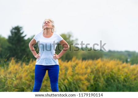 Adult woman with hands on hips looking upwards while wearing blue pants and white tee shirt with blurry yellow flowers in background #1179190114