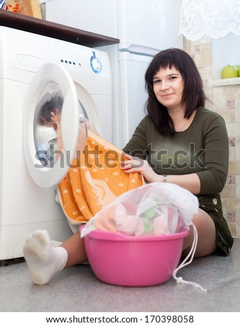 Adult woman with washing machine at her home