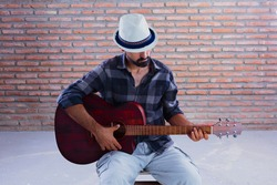 Adult young man with a hat sitting playing an acoustic guitar.