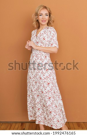 adult young woman is resting in a beautiful feminine blue dress in a bright room by the window relax rest break anticipation anticipation date Foto stock ©