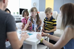 Adults and children are sitting around table on which playing cards are located girl reaches for card with her hand. Family board games for kids and adults at home concept