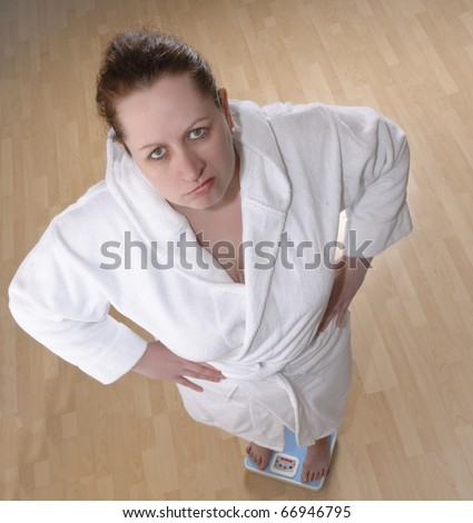 Adults are overweight woman standing on a bathroom scale, she is dressed in a white bathrobe, looking sadly into the camera.