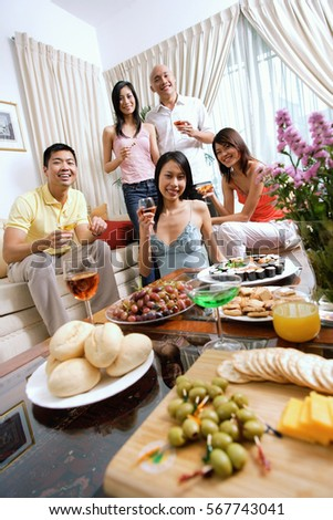 Adults in living room, having a party, smiling at camera, food in the foreground #567743041