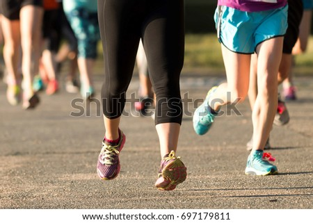 Adults legs racing a 5K at a New York State Park in the early evening over the summer.