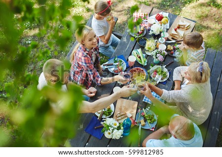 Adults toasting with wineglasses by served table during family dinner
