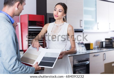 Adutl couple is choosing material for countertop for their future kitchen.  Stock photo ©