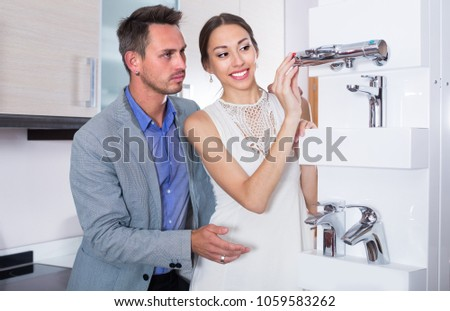Adutl couple is choosing new mixer tap in kitchen furnishing store.  Stock photo ©
