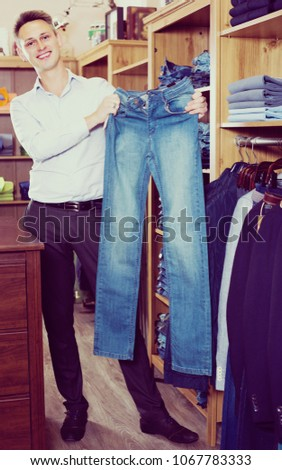 Adutl man is choosing on new jeans in men's clothes store.  Stock photo ©