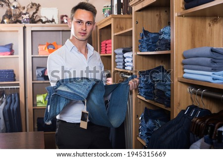Adutl man is choosing on new pants in men's clothes store. Stock photo ©