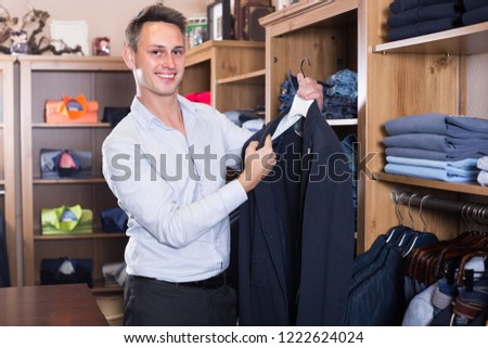 Adutl man is deciding on for new dark blue suit in male clothes store.  Stock photo ©