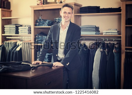 Adutl man is trying on new dark blue jacket in male clothes store.  Stock photo ©