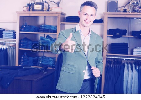 Adutl man is trying on new emerald jacket in male clothes store. Stock photo ©