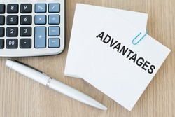Advantages symbol. Concept word 'advantages' on white note on wooden table. Business and advantages concept, copy space.