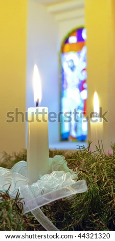 advent candles on the wreath against stained-glass window