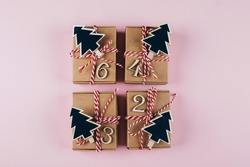 Advent christmas calendar. Wrapped gifts on pink background. Top view, flat lay