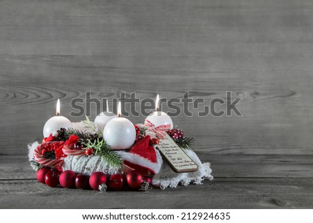 Advent crown with three candles in red and white on grey wooden background.