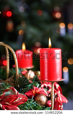 Advent wreath with burning red candles, Christmas tree on background