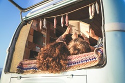 adventure at the sunset, Hipster couple mum and son traveling together on vintage van transport. Life inspiration concept with hippie people on minivan, reading a book together. Warm sunshine