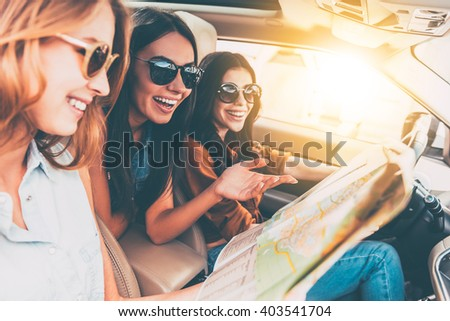 Adventure begins right now! Side view of three beautiful young cheerful women looking away with smile while sitting in car