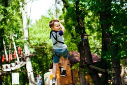 Adventure climbing high wire park - little boy on course in mountain helmet and safety equipment