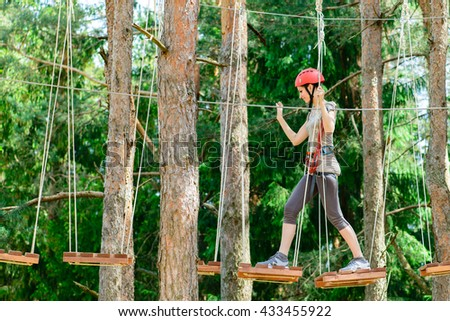 adventure climbing high wire park - Young woman on course in mountain helmet and safety equipment