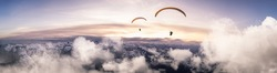 Adventure Composite Image of Paraglider Flying up high in the Rocky Mountains. Sunny Sunset Sky. Aerial Background from British Columbia, Canada. Extreme Sport Concept. Panorama