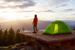 Adventure Girl and Camping Tent on top of a Mountain with Canadian Nature Landscape in the Background during colorful sunset. Taken on Bowen Island, near Vancouver, British Columbia, Canada.