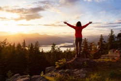 Adventure Girl on top of a Mountain with Canadian Nature Landscape in the Background during colorful sunset. Taken on Bowen Island, near Vancouver, British Columbia, Canada.