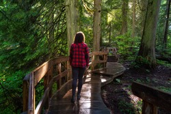 Adventure Girl Walking on a Wooden Pathway in the Rain Forest during a vibrant sunny day. Taken on Giant Cedars Boardwalk Trail in Mt Revelstoke National Park, British Columbia, Canada.
