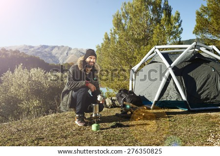 Adventure hiking man with coffee and backpack relaxing after outdoor activity.  Hikers sitting in grass near tent smiling happy outdoors in mountain forest enjoying sun. Conceptual scene.  #276350825