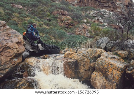 Adventure man crossing river on extreme hike in mountains alone
